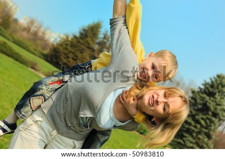 Little boy and his mother are playing outdoor - stock photo