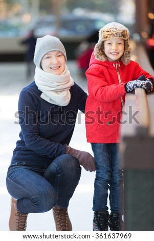 little boy and his mother ice skating together at outdoor skating rink, having winter vacation fun - stock photo
