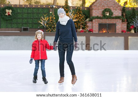 little boy and his mother ice skating together at outdoor skating rink with holiday decorations, having winter vacation fun - stock photo