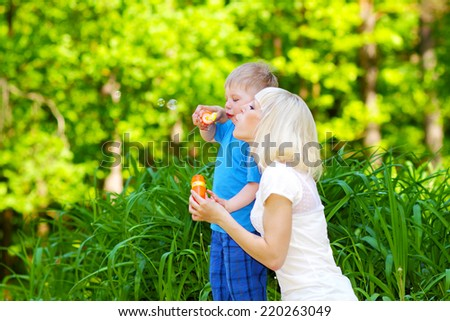 little boy and his mother with soap bubbles outdoors