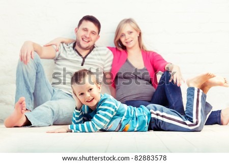 Little boy and his parents on the floor near the wall. Mother is pregnant.