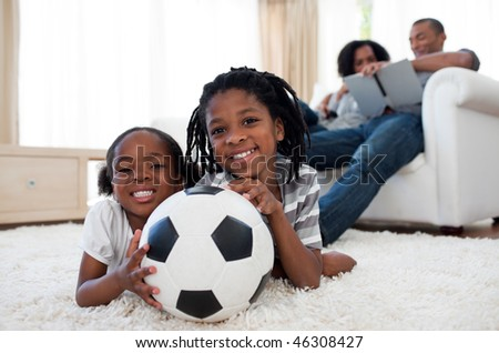 Little boy and his sister holding soccer ball lying on the floor - stock photo