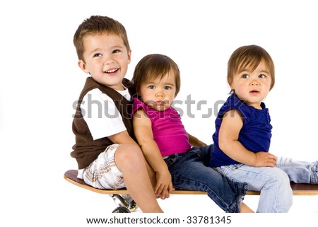 Little boy and his twin sisters on a skateboard - stock photo