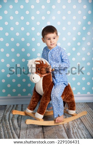 Little boy and horse - rocking chair - stock photo