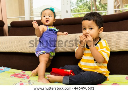 little boy and little girl eating french fries in home with happiness.
