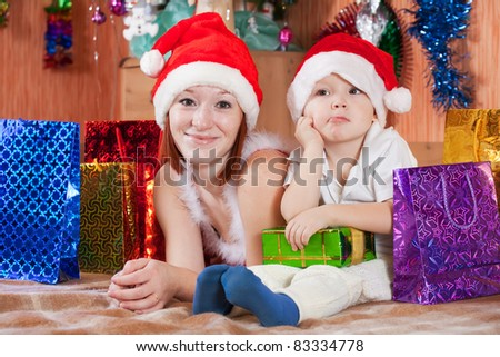 Little boy and mother in Santa hat at home - stock photo