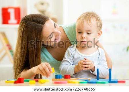 little boy and mother play with building blocks - stock photo