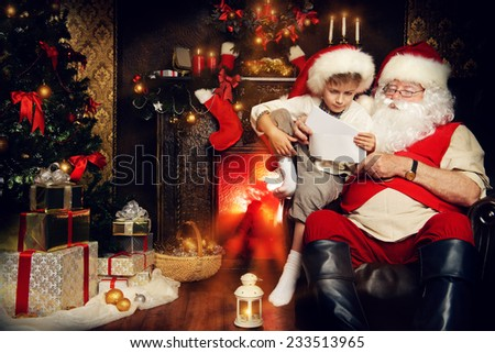 Little boy and Santa Claus reading letters from children. They are at home, decorated for Christmas. Santa's mail.  - stock photo