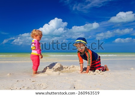 little boy and toddler girl building sandcastle on summer beach