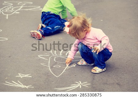 little boy and toddler girl drawing rocket on asphalt, kids outdoor activities - stock photo