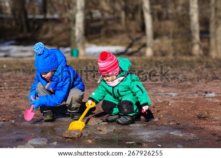 little boy and toddler girl playing with water in spring
