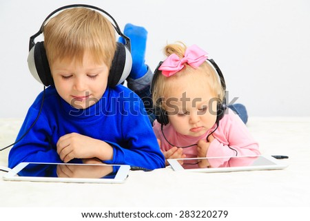 little boy and toddler girl with headset using touch pad, early education and learning - stock photo