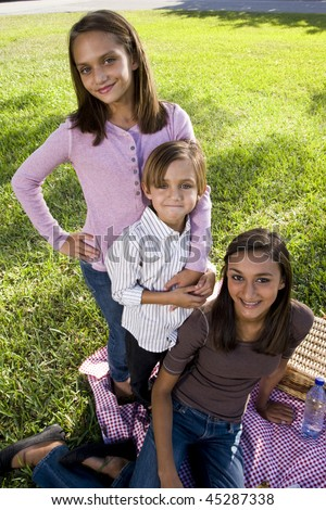 Little boy and two older sisters posing for camera sitting on picnic blanket in park - stock photo