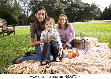 Little boy and two sisters having picnic in park - stock photo