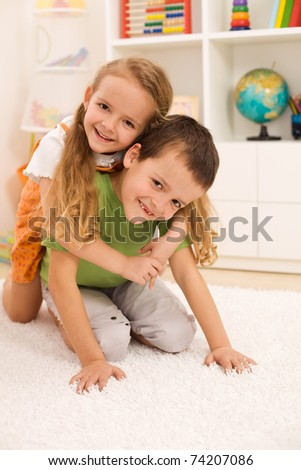 Little boy anf girl wrestling and having fun in their room - stock photo
