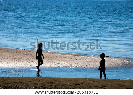 Little boy ang girl silhouettes in counter light on a river bank - stock photo