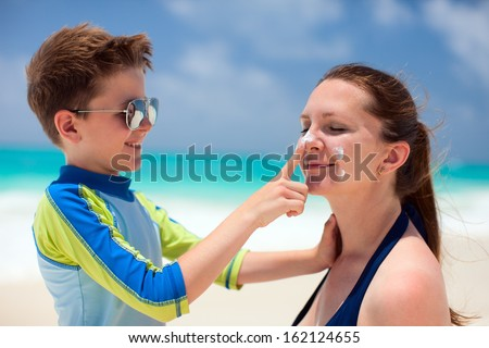 Little boy applying sun cream to her mother nose - stock photo