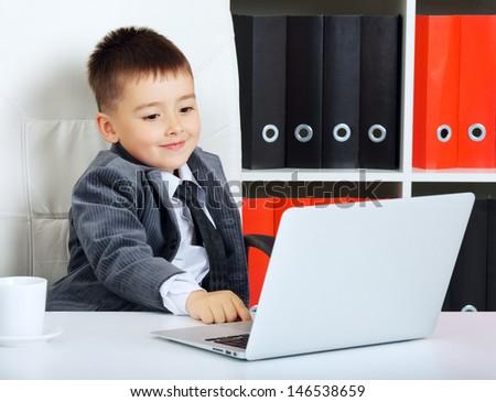 little boy as a businessman, in office - stock photo