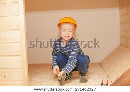 Little boy as a construction worker with hammer and hellmet.