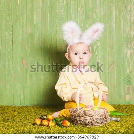 Little boy as a Easter rabbit on the grass with colorful eggs