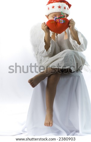 little boy as angel in red xmas hat with toy heart - stock photo