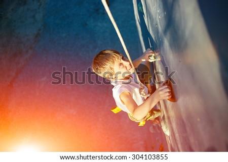 Little boy ascending in outdoor rock climbing gym - stock photo