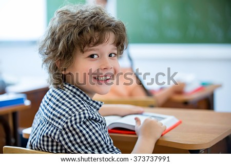 Little boy at a desk in classroom - stock photo