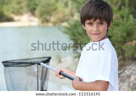 Little boy at a riverside with a landing net - stock photo