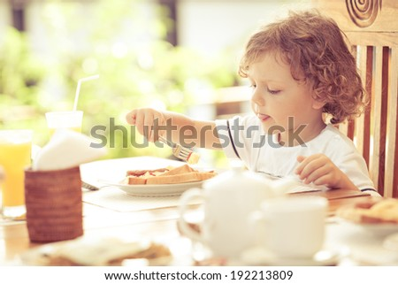 little boy at breakfast - stock photo
