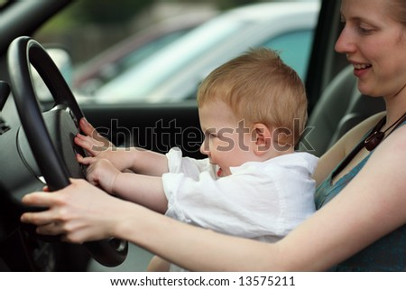 Little boy at drivers seat together with mother. Shallow DOF. - stock photo