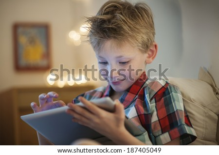 little boy at expressive face using a digital tablet in bed - stock photo
