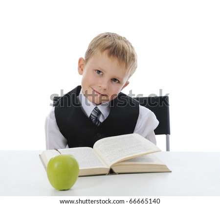 little boy at his desk with books and apple. Isolated on white background - stock photo