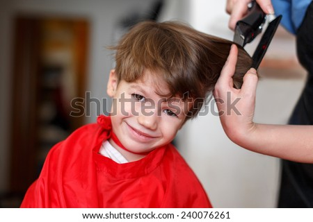 Little boy at professional barber, hair saloon - stock photo