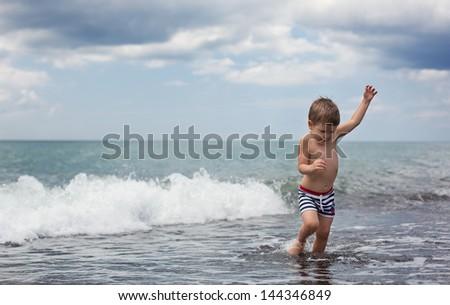 Little boy at sea beach - stock photo