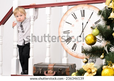 little boy at stair rails with big clock in christmas interior - stock photo
