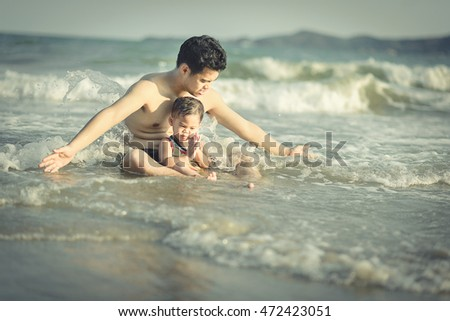little boy at the beach and father protect his son from wave
