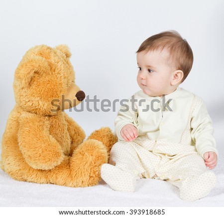Little boy baby sitting next to a teddy bear. On white. - stock photo