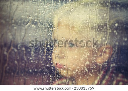 Little boy behind the window in the rain - selective focus - stock photo