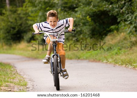 Little boy being really fast on his bicycle - stock photo