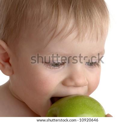 little boy bites a green apple. on white - stock photo