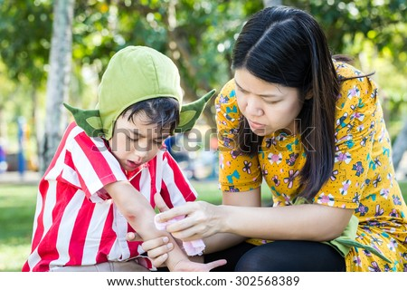 Little boy bleeding arm wound near elbow and mother help first aid to him - stock photo