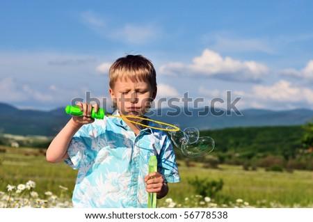 little boy blowing soap bubbles in daisy field - stock photo