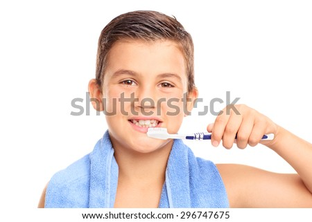 Little boy brushing his teeth with a toothbrush and looking at the camera isolated on white background - stock photo