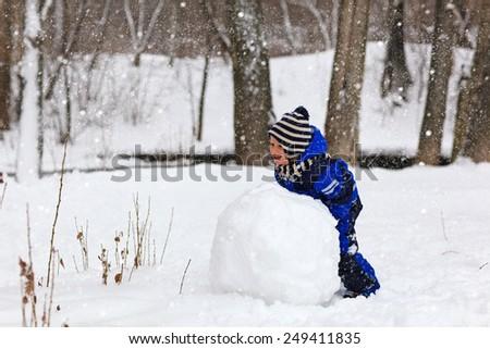 little boy building snowman in winter park - stock photo