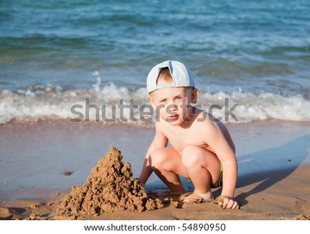 little boy builds a sand house on a beach - stock photo