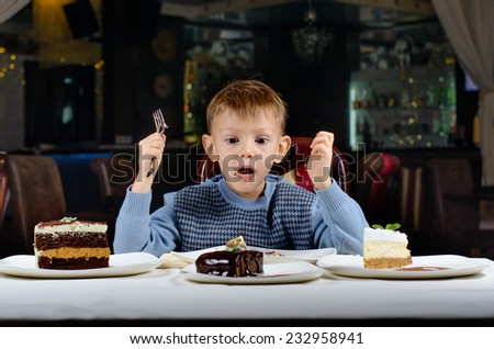 Little boy cannot believe his luck as he sits at the dining table holding a fork gawping at an array of different cakes spread out in front of him in wonderment