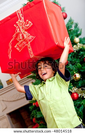 Little boy carrying a christmas present and smiling - stock photo