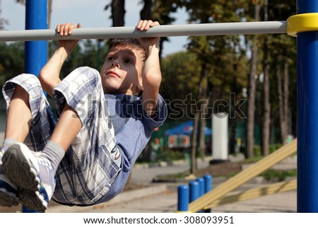 Little boy catch up on the horizontal bar, active childhood, cute small acrobat