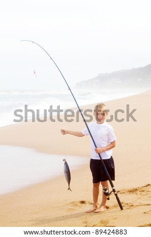 little boy catching a big fish on beach - stock photo