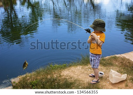 Little Boy Catching a Fish - stock photo